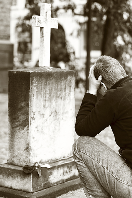 Man mourning at grave site