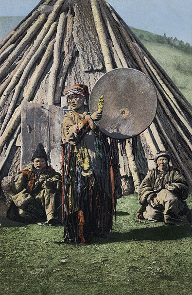 female shaman in full garments with large drum in front of log teepee in Mongolia