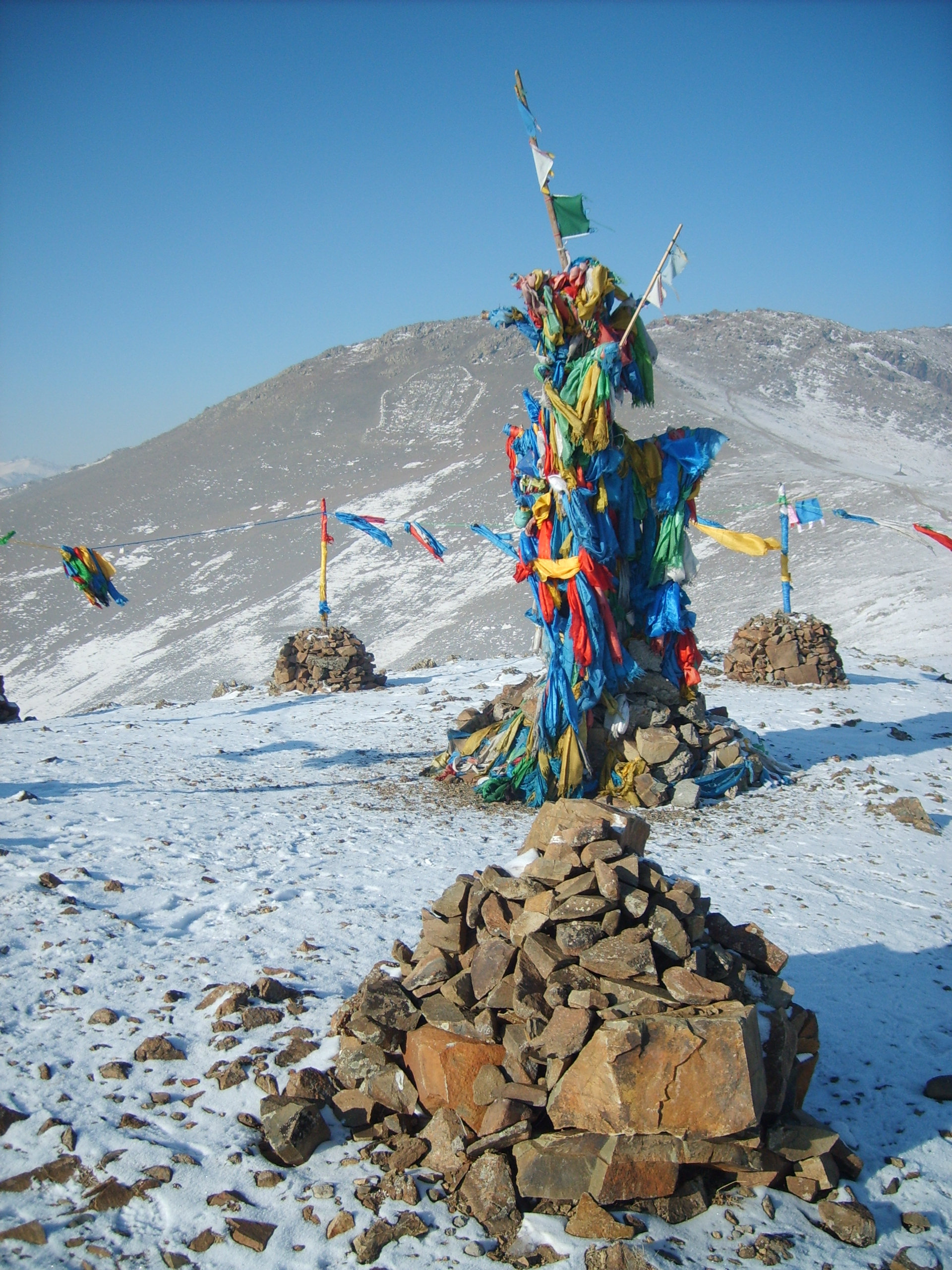 pile of rocks in front of colorful totem of materials on Mt. Chingeltei Uul in Mongolia