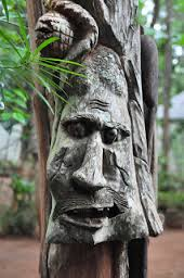 carved wooden mask on tree